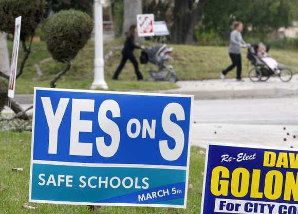 "A small group of walkers are seen in the backgroung of a ""Yes on S"" sign placed on the 1500 block of 6th St. in Burbank on Tuesday, February 5, 2013."