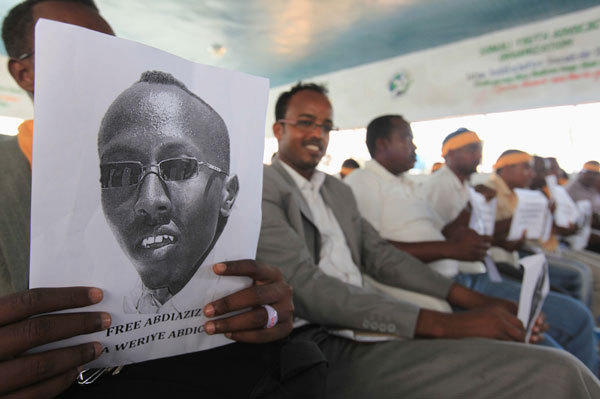 A Somali journalist holds a poster bearing the image of Abdiaziz Abdinur Ibrahim as they demand for his release in capital Mogadishu January 27, 2013. Abdiaziz was reportedly arrested after reporting on a rape case allegedly involving government soldiers according to local media reports.