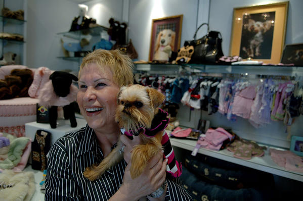Marilyn Belkin of Delray Beach shows off her dog, Mitzi Bitzi, a 6-pound Brussels Griffon, as she tries on outfits at Chateau Poochie, a luxury dog resort and spa in Lighthouse Point.