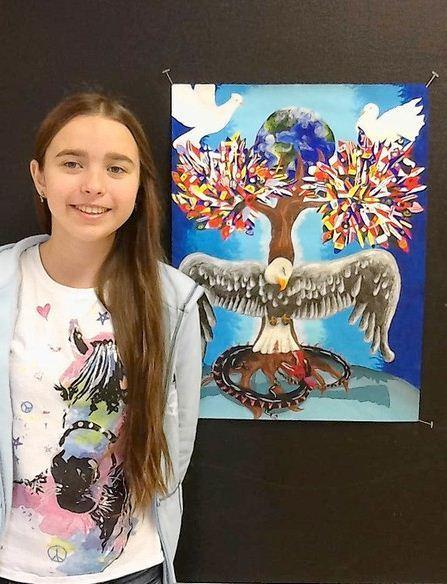 Anastasiia Sevriukova, 13, stands next to her winning poster.