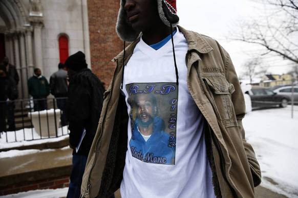 A young man who said he was a relative to Norman Stokes, 38, whose image is on the t-shirt, stands outside at the conclusion of a funeral at St. Andrews Temple in Chicago. Stokes was shot during a dice game in Englewood.