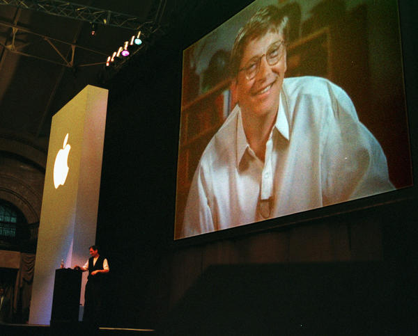 In 1997, Apple interim Chief Executive Steve Jobs, seen at the podium, had a big surprise for Macworld attendees: Rival Microsoft had thrown Apple a lifeline by agreeing to invest $150 million to keep the company afloat. As the announcement is made, a gigantic image of Microsoft CEO Bill Gates appears on a video screen behind Jobs, as the audience gasps.