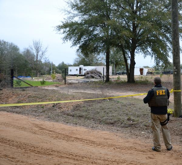 FBI agents and sheriff's deputies secure the scene where Ethan, 5, was held captive for nearly a week. The kidnapper lived in the white trailer and held the boy in an underground bunker.