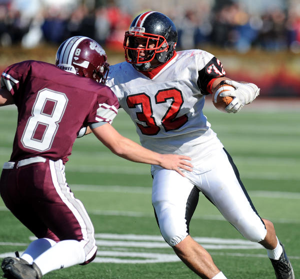 Easton #32 Austin Brown is defended by Phillipsburg #8 Chris Trent in their football game held at Lafayette College's Fisher Field on Thanksgiving.