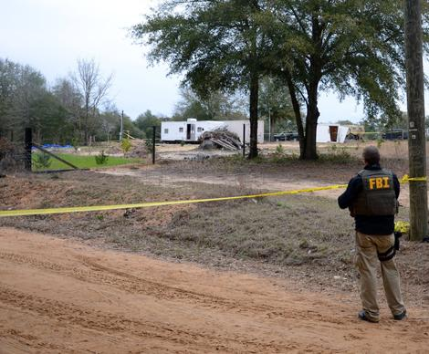 FBI agents and Dale County sheriff's deputies secure the residence in Midland City, Ala., where a 5-year-old child was rescued after being held hostage for almost a week by Jimmy Lee Dykes. The boy was rescued and his captor was killed Monday when federal agents raided the bunker.