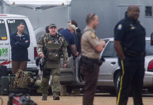 An FBI bomb technician, other agents and Alabama state troopers prepare to process the crime scene Tuesday in Midland City, Ala.