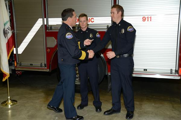 Firefighter-paramedics Bryan Kistler, center, and Joel Whipp, right, receive the Lifesaving Award.