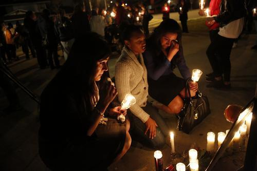 Monica Quan's basketball teammate and friend, Julie Escalera, left, sits with Germita Haynie, center, and Stephanie Escalera as they pay their respects in front of candles and photos of the slain basketball coach.