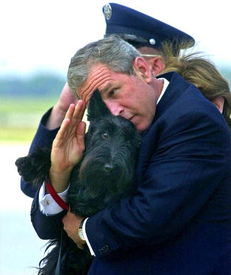 President Bush salutes while holding Barney as they get off Air Force One at Andrews Air Force Base.