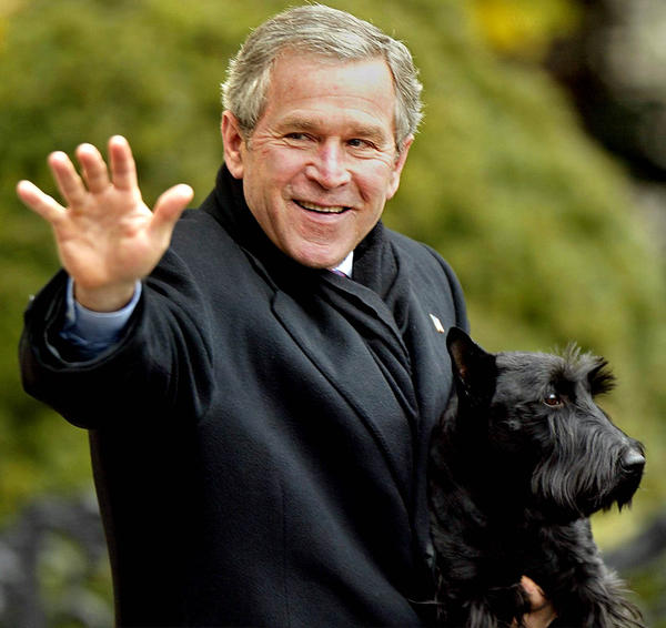 President George W. Bush holding with Barney outside the White House.