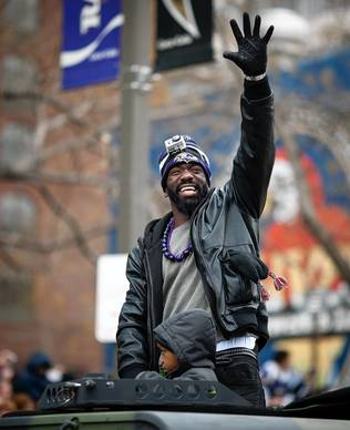 Ed Reed, center, rides atop a Hummer during the parade. He is wearing a GoPro video camera strapped to his head.