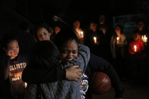 Kendra Carraway, a high school basketball teammate of Monica Quan's, hugs a friend during a memorial vigil for Quan at Walnut High School on Monday in Walnut. Keith Lawrence, 27, and Quan were found shot to death in a parked car in an upscale Irvine condominium complex where the couple lived. Quan was the assistant women's basketball coach at Cal State Fullerton.