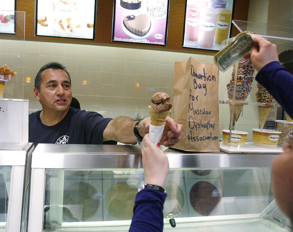 Firefighter/paramedic Ruben Mercado with the Burbank Fire Department smiles as he hands off a free ice cream cone as a donation is being placed in the bag at Haagen-Dazs in the Burbank Town Center on Tuesday, February 5, 2013. The firemen were giving out free scoops of ice cream and asking for donations to the Muscular Dystrophy Association.