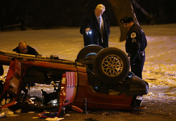 Officials examine a Jeep that crashed and killed three near 31st Street and Western Avenue.