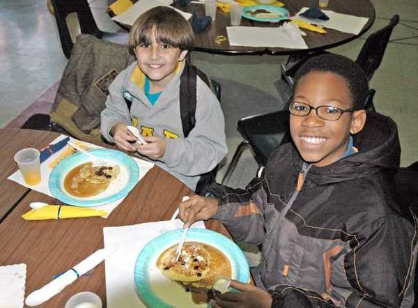 Sixth-grader Rami Makarem, 11, left, who achieved straight A's, and sixth-grader David Miller II, also 11, who earned three A's, enjoy their pancake breakfast at Jordan Middle School in Burbank.