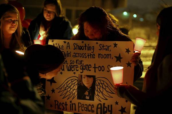 Denise Lozano holds a poster honoring slaying victim Abigail Villalpando, 18, during a candlelight vigil Tuesday in Aurora. Ricky Villalpando looks at the picture of his sister.