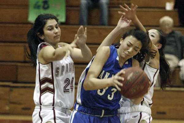 La Canada's Aundrea Issakhanian, left, and Courtney Chen, right, play defense on San Marino's Tiffany Meihls in a 48-41 Spartans' victory.