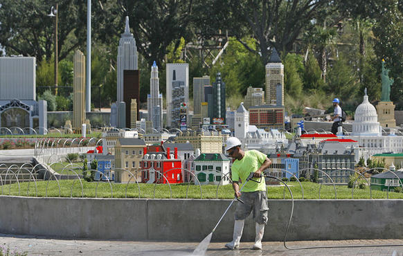 A worker power washes the grounds at Legoland Florida in front of Miniland USA in Winter Haven, Fla. Tuesday, September 13, 2011.
