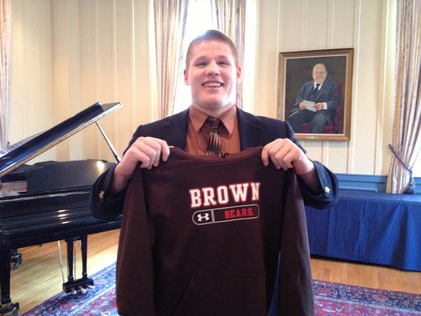 Cheshire Academy's Jeff Biestek shows off his new favorite team after signing his letter to attend Brown on Wednesday.