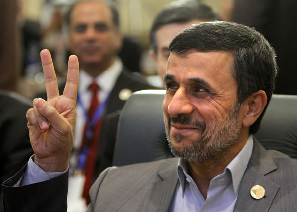 Iranian President Mahmoud Ahmadinejad flashes the victory sign as he attends the 12th summit of the Organization of Islamic Cooperation in Cairo on Wednesday. Saeed Mortazavi, a key ally, was said to be released from custody Wednesday in Iran after being jailed on what were reportedly corruption charges.