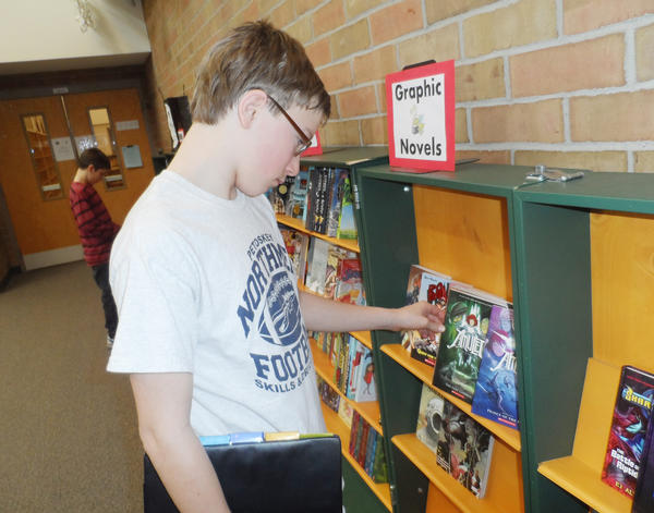 Austin Stokel, an eighth-grader at Petoskey Middle School, looks for a book to buy at the book fair sponsored by the middle school library and McLean and Eakin Booksellers.