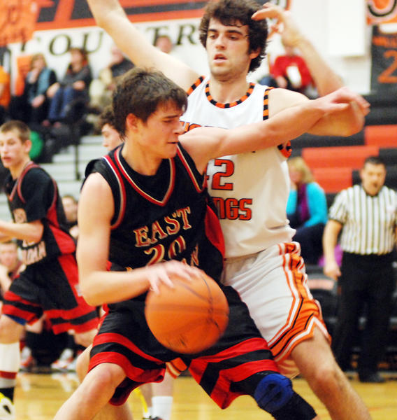 East Jordans Isaiah Sladick (left) looks to work his way inside as Harbor Springs senior Neal Zoerhof defends during Tuesdays Lake Michigan Conference contest at the Harbor Springs High School gym. The Rams defeated the Red Devils, 60-38.