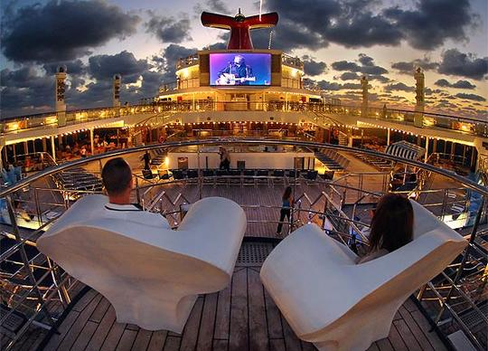 "Located poolside on Lido Deck of Carnival Cruise Line's Carnival Glory's is the new ""Seaside Theatre,"" a massive 270-square-foot LED screen that displays movies, concerts, sporting events, and other programming, including the popular ""Morning Show"" hosted by the ship's cruise director.  Utilizing the same technology featured in large stadiums and New York's Times Square, the state-of-the-art entertainment system includes a 70,000-watt sound system, providing concert quality sound, even outdoors."