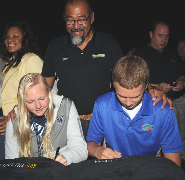 Under the watchful eye of American Heritage Plantation swim coach Nobutaka Tan, center, swimmers Jessie Randolph (Villanova), left, and Daniel Spas (University of Florida) signed their national letters of intent on Wednesday in the school's theater. They were among 22 student-athletes at the school who signed with colleges.