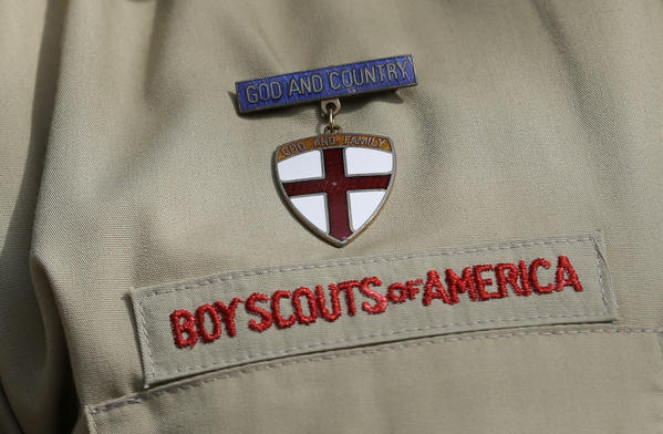 This photo taken Monday shows a close up detail of a Boy Scout uniform worn by Brad Hankins, a campaign director for Scouts for Equality, as he responds to questions during a news conference in front of the Boy Scouts of America headquarters in Irving, Texas. The Boy Scouts of America put off a decision Wednesday on whether to lift its ban on gay members and leaders, saying the question will be taken up at the organization's national meeting in May.