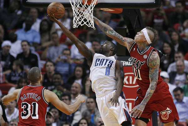 Charlotte Bobcats' Ben Gordon tries for the layup as Miami Heat's Chris Andersen defends.