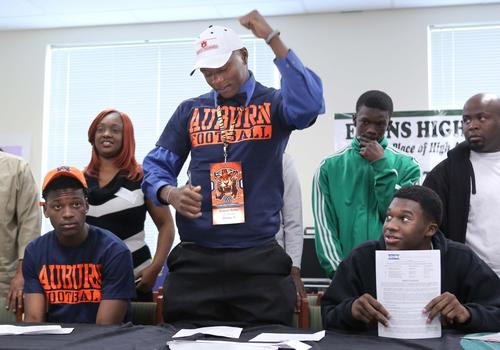 During a National Signing Day ceremony at Evans High School, football player Dominic Walker (signing to Auburn) celebrates, with Tony Stevens (left, signing to Auburn), and James Julius (right, signing to The Citadel), in Orlando, Fla., Wednesday, February 6, 2013.