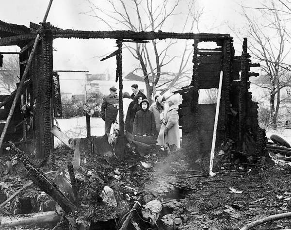 Neighbors look at the ruins of a home on the 15800 block of 113th Court on Dec. 30, 1968. Five people were killed in the fire.