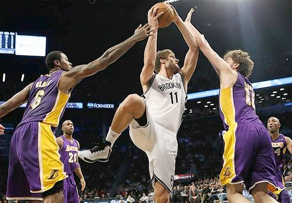 Brooklyn Nets' Brook Lopez (C) shoots over Los Angeles Lakers' Pau Gasol (R) and Earl Clark.