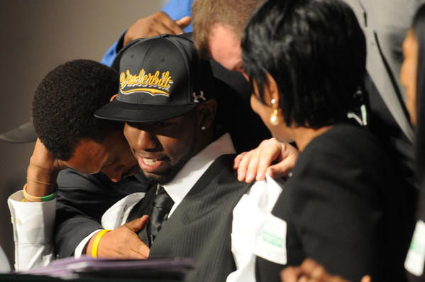 University School football player Jordan Cunningham is hugged by (left) head football coach Roger Harriet after announcing he was signing with Vanderbilt University during National Signing Day at University School Wednesday morning in Davie.  Cunningham was surrounded by his family and coaches as his announcement was televised on ESPN.