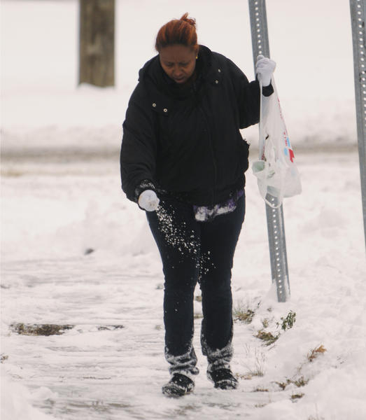 Warda Galbeti Blackwood applies salt to the sidewalk corner of South Whitney Street and Warrenton Street in Hartford, Conn.