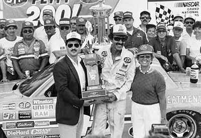 Daytona Firecracker 400 winner Richard Petty in Victory Lane wearing his tell-tale sunglasses. His wife Linda stands at right.
