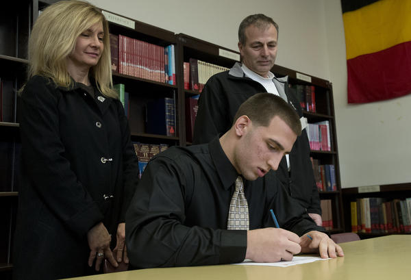 Andrea and Keith Kauffman of Bethlehem Township watch as their son - Freedom High School football player Evan Kauffman participates in a mock contract signing for Lehigh University during National Signing Day on Wednesday.