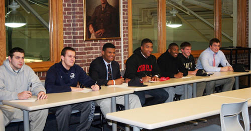 From left to right, Gilman athletes Nick Fertitta (American International football), Alex Foertsch (Virginia football), Micah Kiser (Virginia football), Miles Norris (Cornell football), Jibri McLean (Kenyon football), Tanner Vosvick (United States Military Academy soccer) and Henry Poggi (Michigan football) take part in a ceremony at the school.