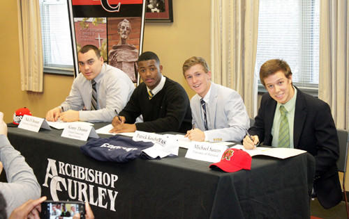 From left to right, Archbishop Curley athletes Nik D'Avanzo (New Mexico football), Kenny Thomas (Central Connecticut State football), P.J. Kosher (Georgetown soccer) and Michael Sauers (Maryland soccer) take part in a ceremony at the school.