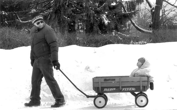 A West Hartford family finds some reprieve after the storm, strolling the snow-covered area.