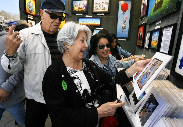 "Jackie Buttice, center, with Sam Dittmer and his wife, Sandy, browse the ""Sheep Incognito by Conni Togel"" booth during the Mount Dora Arts Festival on Saturday. Mount Dora Center for the Arts staff and downtown merchants generally agreed the show was a success."