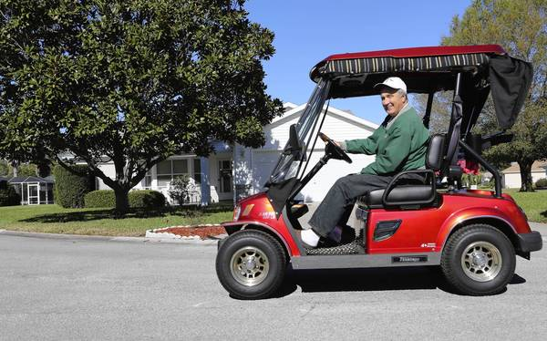 Jerry Dillen with his golf cart at The Villages on Jan. 31, 2013. Dillen, purchased a Tomberlin low-speed vehicle for its safety features and ability to go up to 25 miles an hour. A traditional golf cart only goes 20 mph and are not allowed on most roadways, unlike Dillen's Tomberline.