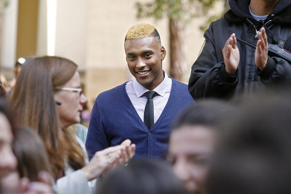 Glendale High School's Michael Davis is all smiles as the crowd in the quad applaud him as he is recognized for his accomplishment of a full-ride scholarship to BYU that his is about to sign in Glendale on Wednesday, February 6, 2013. Davis signed a letter of intent for a full-ride scholarship to Brigham Young University, the first time at Glendale High School since 1992.