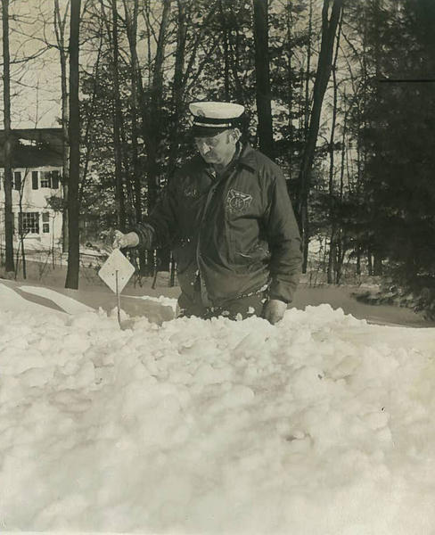 A fire chief in the Simsbury area holds a piece of identification to mark a snow-covered fire hydrant.