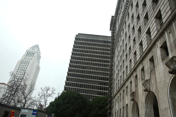 The facade of the County Hall of Justice, right, is dark and dirty compared with that of Los Angeles City Hall, left. The material of both buildings is Sierra white granite, quarried near Fresno. The exterior of the Hall of Justice will soon be cleaned and restored.