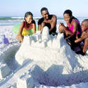 A family builds a sandcastle at the beach in Fort Myers
