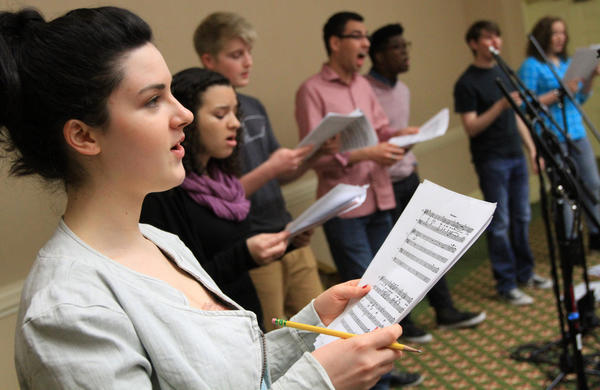 Kate Gratson, a soprano from Brooklyn, N.Y., left, practices with the choir.