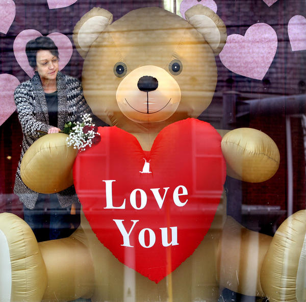 Libby Fravel places a few long-stemmed red roses in the paw of the large inflatable Valentine bear that sits in a front window of the family-owned store, The Flower Center, in Stephens City, Va.