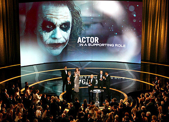 "The face of <a class=""taxInlineTagLink"" id=""PECLB002980"" title=""Heath Ledger"" href=""/topic/entertainment/movies/heath-ledger-PECLB002980.topic"">Heath Ledger</a> as the Joker looms over the crowd as his family comes to the stage to accept his award."