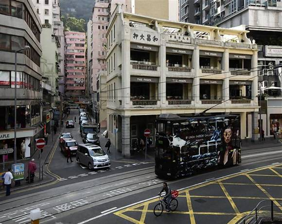 A man rides a bicycle next to a tram passing by a Chinese pawn shop that has been restored and partially converted into a restaurant at Hong Kong's Wanchai district